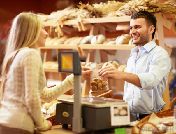 woman-taking-bag-of-food-from-man-behind-the-counter